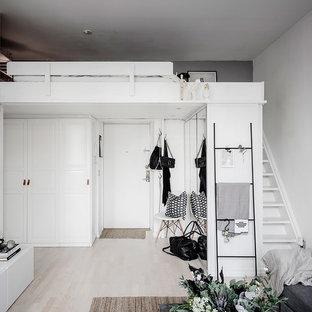 Skandinavisk inredning av en foajé, med grå väggar, ljust trägolv, en enkeldörr, en vit dörr och beiget golv
