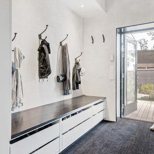 Idéer för ett mellanstort minimalistiskt kapprum, med vita väggar, heltäckningsmatta och svart golv