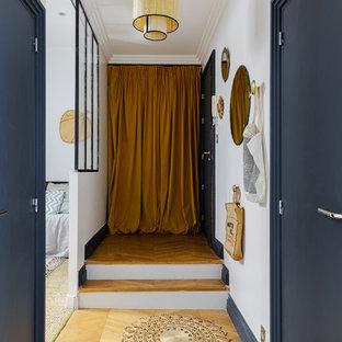 Exemple d'une entrée éclectique de taille moyenne avec un mur blanc, un sol en bois clair et une porte simple.