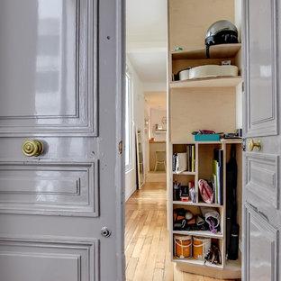 Inspiration pour une grand entrée design avec un couloir, un mur blanc, un sol en bois clair, une porte double et une porte grise.
