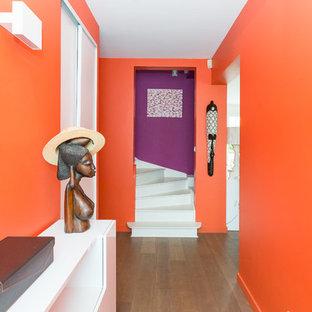 Aménagement d'un grand hall d'entrée contemporain avec un mur orange et un sol en bois foncé.