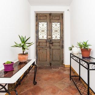 Idées déco pour une porte d'entrée méditerranéenne avec un sol en carreau de terre cuite, une porte double, une porte en bois brun et un sol rouge.