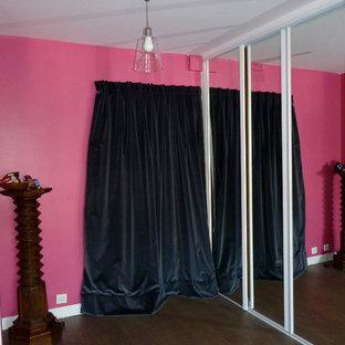 パリの中サイズの片開きドアコンテンポラリースタイルのおしゃれな玄関ロビー (ピンクの壁、淡色無垢フローリング、木目調のドア、グレーの床) の写真