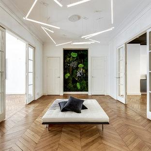 Idée de décoration pour un grand hall d'entrée design avec un mur blanc, un sol en bois clair et un sol beige.