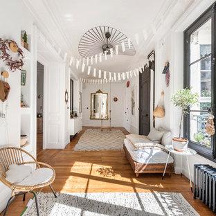 Modelo de hall bohemio con paredes blancas, suelo de madera en tonos medios, puerta simple y puerta negra