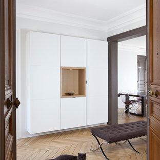 Aménagement d'un grand hall d'entrée contemporain avec un mur blanc, un sol en bois brun, une porte double et une porte en bois brun.