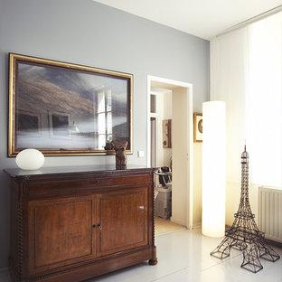 Cette image montre une entrée bohème de taille moyenne avec un mur gris et un sol en bois peint.
