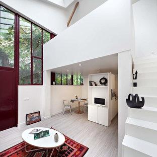 Exemple d'un hall d'entrée tendance de taille moyenne avec un mur blanc, un sol en bois clair, une porte simple et une porte rouge.