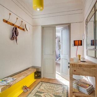 Inspiration pour une entrée bohème de taille moyenne avec un mur beige, un sol en bois clair et un vestiaire.