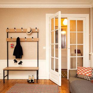 Foto på ett mellanstort skandinaviskt kapprum, med orange väggar och ljust trägolv
