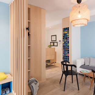 Example of a mid-sized danish plywood floor and beige floor entryway design in Lyon with blue walls and a glass front door