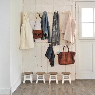 Aménagement d'une entrée campagne avec un vestiaire, un mur blanc, un sol en bois foncé, une porte simple et une porte blanche.
