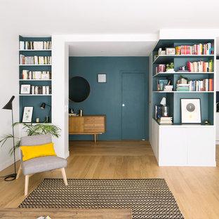 Réalisation d'un hall d'entrée design de taille moyenne avec un mur bleu, un sol en bois clair, une porte simple, une porte bleue et un sol beige.