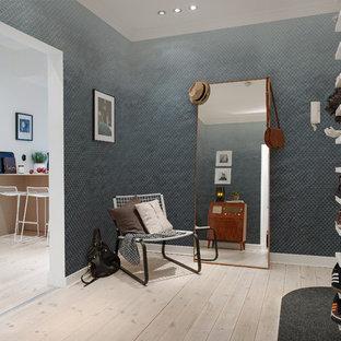 Cette photo montre une entrée tendance de taille moyenne avec un vestiaire, un mur bleu et un sol en bois clair.