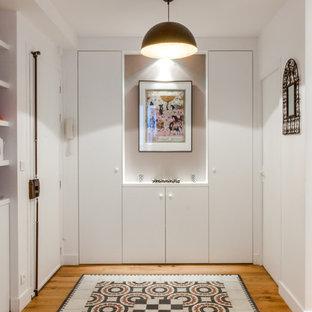 Inspiration pour un grand vestibule design avec un mur blanc et un sol en bois brun.