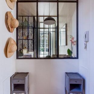 Cette photo montre un vestibule tendance de taille moyenne avec un mur blanc et un sol en bois brun.