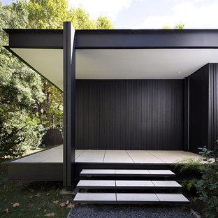 Cette photo montre une porte d'entrée moderne de taille moyenne avec un mur noir, un sol en carrelage de céramique, une porte simple, une porte noire et un sol blanc.