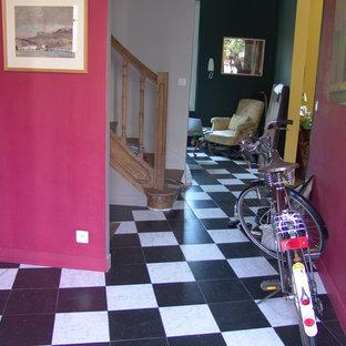 Cette image montre un hall d'entrée bohème de taille moyenne avec un mur rose, un sol en carrelage de céramique, une porte simple et une porte en bois brun.