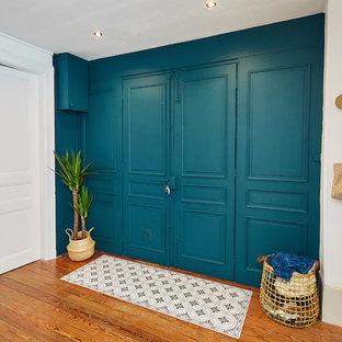 Immagine di un ingresso o corridoio moderno con pareti blu e parquet scuro