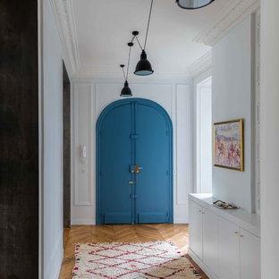 Exemple d'une entrée tendance avec un couloir, un mur blanc, un sol en bois brun, une porte double, une porte bleue et un sol marron.