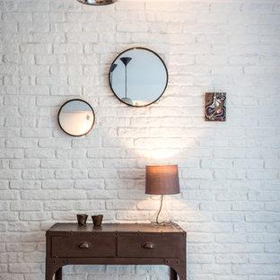 Réalisation d'une entrée bohème de taille moyenne avec un mur blanc, un couloir, un sol en bois clair et un sol gris.