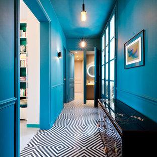 パリの中くらいの両開きドアエクレクティックスタイルのおしゃれな玄関ホール (青い壁、黒い床、セラミックタイルの床) の写真