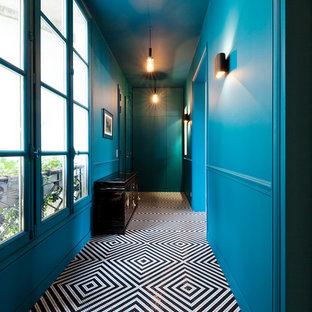 パリの中くらいの両開きドアエクレクティックスタイルのおしゃれな玄関ホール (青い壁、黒い床、セラミックタイルの床、青いドア) の写真