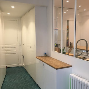 Large trendy terra-cotta floor and blue floor entryway photo in Paris with white walls and a white front door