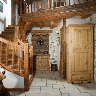 Cette image montre un hall d'entrée chalet de taille moyenne avec un mur blanc et une porte en bois brun.