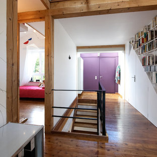 Idée de décoration pour un très grand hall d'entrée design avec un mur blanc, un sol en bois brun et une porte violette.
