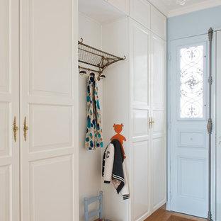Exemple d'une entrée chic de taille moyenne avec un vestiaire et un sol en bois brun.