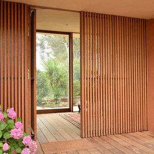 Inspiration för en stor orientalisk ingång och ytterdörr, med mellanmörkt trägolv och en enkeldörr
