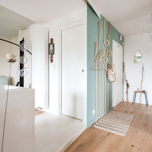 Example of a small arts and crafts light wood floor entryway design in Le Havre with green walls and a white front door