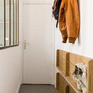 Свежая идея для дизайна: маленькая узкая прихожая в современном стиле с белыми стенами, бетонным полом, одностворчатой входной дверью, белой входной дверью и серым полом - отличное фото интерьера