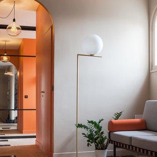 Cette image montre un grand hall d'entrée méditerranéen avec un mur gris, une porte simple, une porte orange et un sol beige.