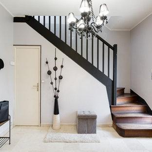 Réalisation d'un hall d'entrée bohème avec un mur gris, une porte simple, une porte blanche et un sol beige.