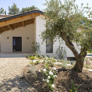 Idée de décoration pour une porte d'entrée méditerranéenne avec un mur blanc, une porte simple et une porte noire.