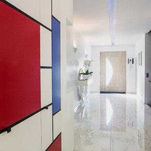 Exemple d'un grand hall d'entrée tendance avec un mur multicolore et un sol en marbre.