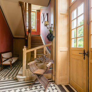 Example of an ornate multicolored floor entryway design in Paris with red walls and a glass front door