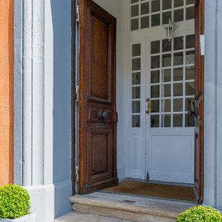 На фото: входная дверь в классическом стиле с серыми стенами, двустворчатой входной дверью и входной дверью из темного дерева с