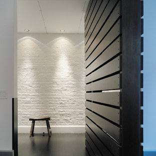 Small minimalist dark wood floor entryway photo in New York with white walls and a dark wood front door