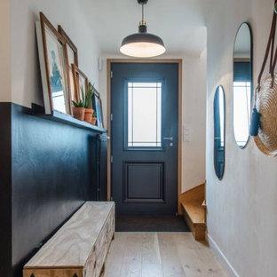 Exempel på en liten eklektisk hall, med svarta väggar, ljust trägolv, en enkeldörr och en svart dörr
