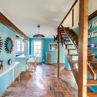 Exemple d'un grand hall d'entrée éclectique avec un mur bleu et un sol en carreau de terre cuite.