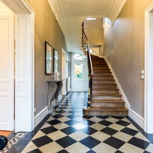 Idée de décoration pour une entrée tradition avec un couloir, un mur beige, un sol multicolore, une porte double et une porte blanche.