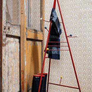 Cette image montre une entrée bohème avec un vestiaire, un mur multicolore, un sol en bois brun, une porte coulissante et une porte en bois brun.