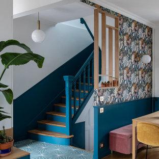 パリの中くらいの片開きドアモダンスタイルのおしゃれな玄関ロビー (青い壁、コンクリートの床、グレーのドア、青い床) の写真