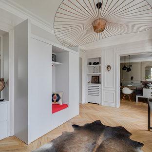 Cette photo montre un hall d'entrée tendance avec un mur gris et un sol en bois clair.
