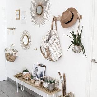 Cette photo montre un hall d'entrée bord de mer avec un mur blanc, béton au sol, une porte blanche et un sol gris.