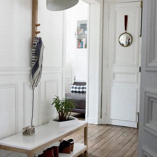 Inspiration pour une entrée design de taille moyenne avec un mur blanc et un sol en bois brun.