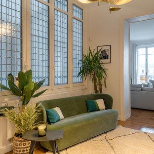 Idées déco pour une entrée classique avec un mur blanc, un sol en bois brun et un sol marron.